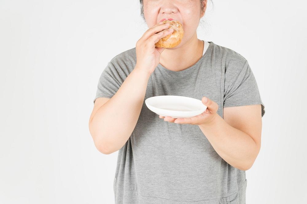 太った女性がシュークリームを食べる