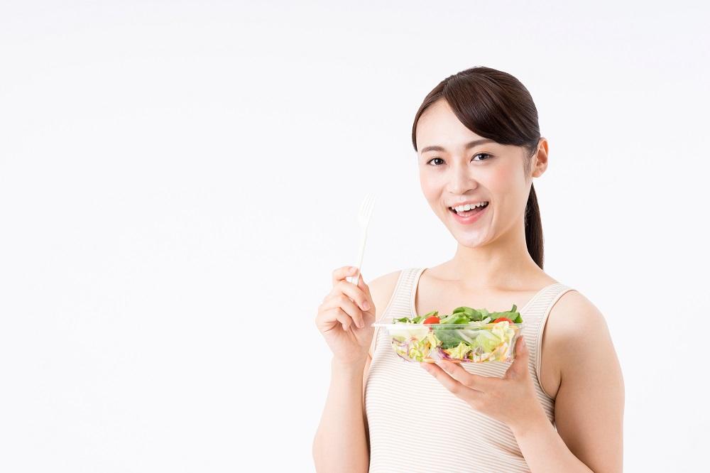野菜サラダを持った女子